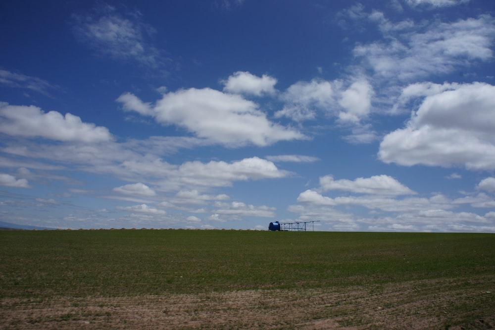 green plain field under cloudy sky