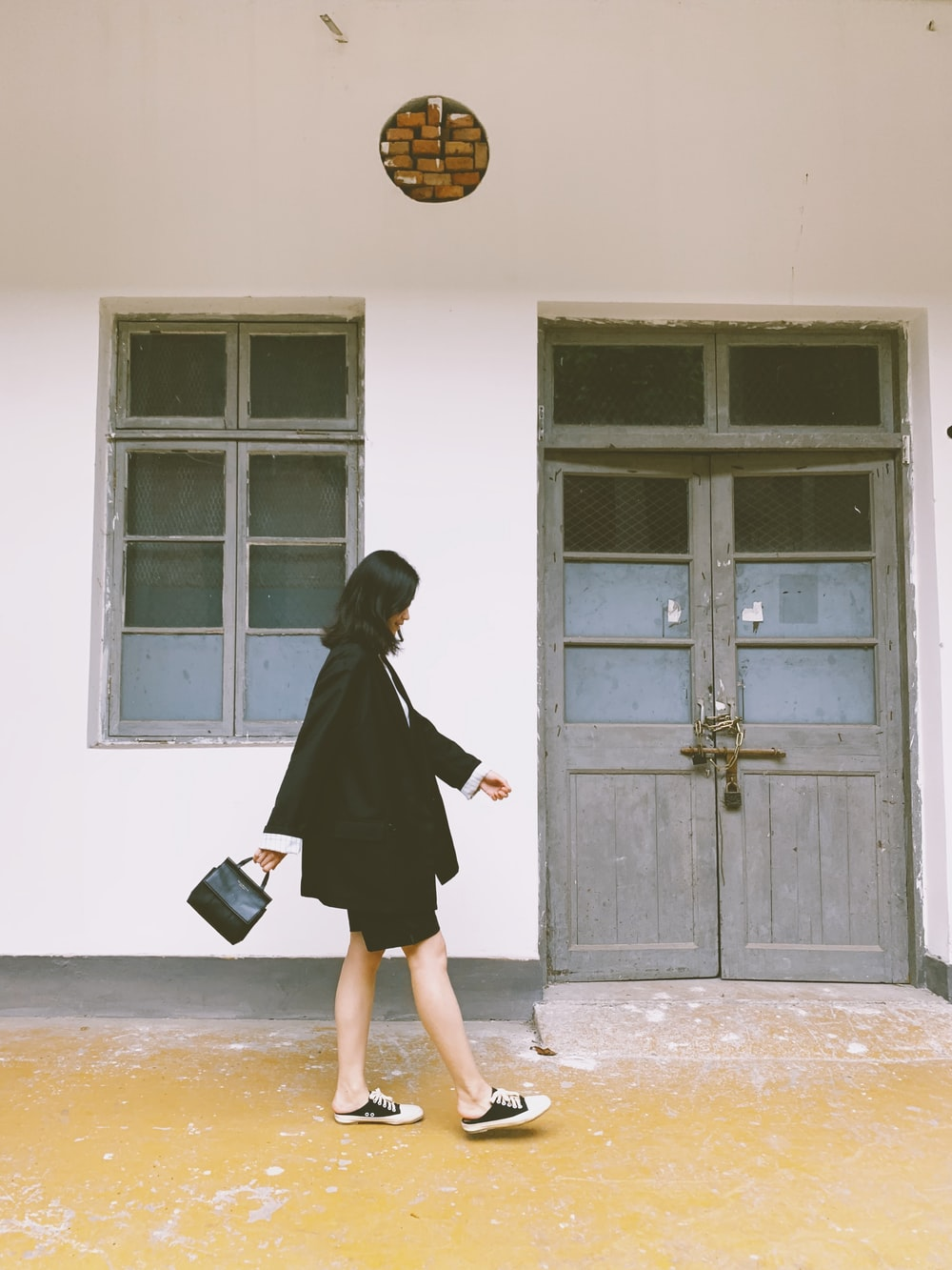 woman in black blazer walking and carrying black handbag