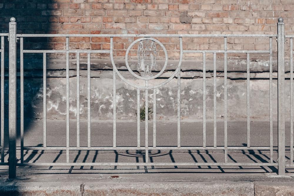white metal fence near wall
