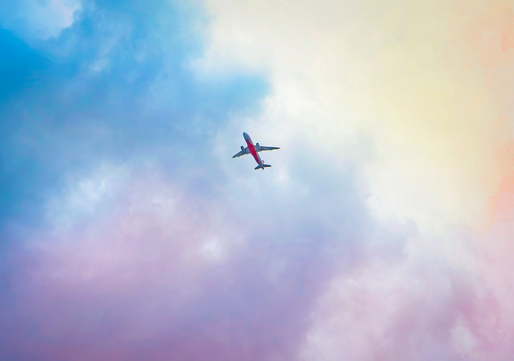 red and white airplane under clear blue sky