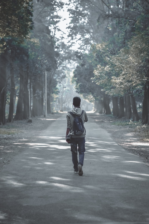 man in grey hooded jacket walking on grey concrete road