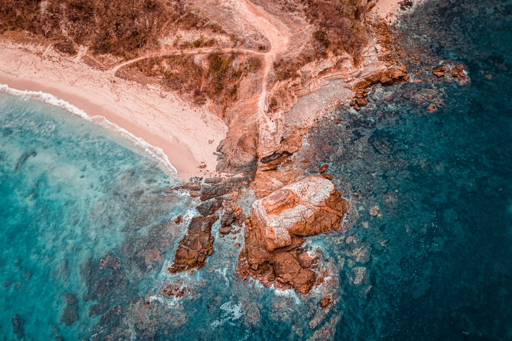aerial photography of brown rock formation beside seashore
