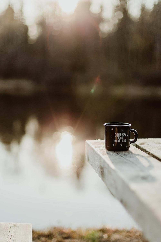 black mug on dock near lake