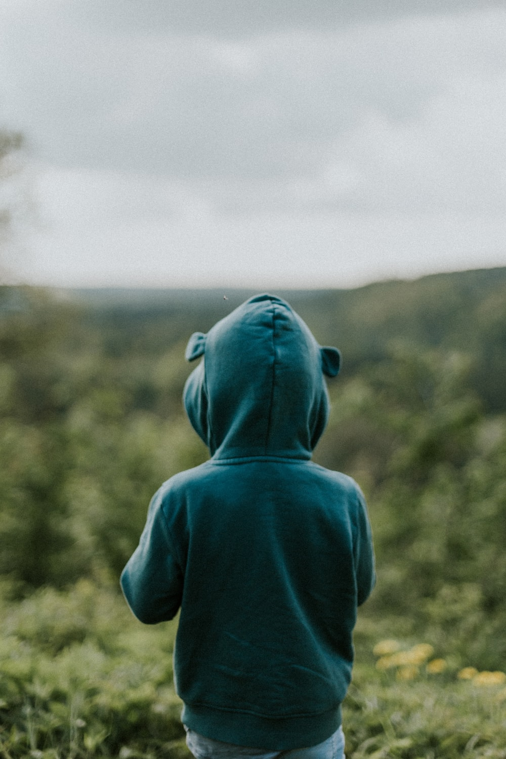kid wearing green hoodie close-up photography