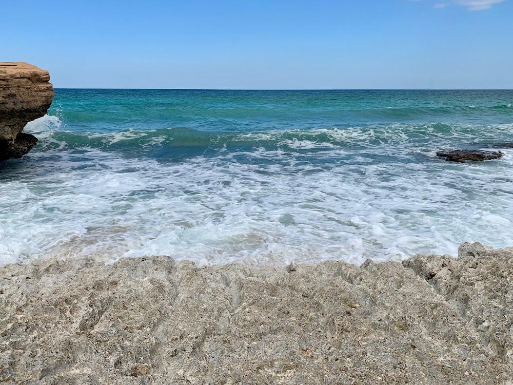 sea wave splashing on rock formation