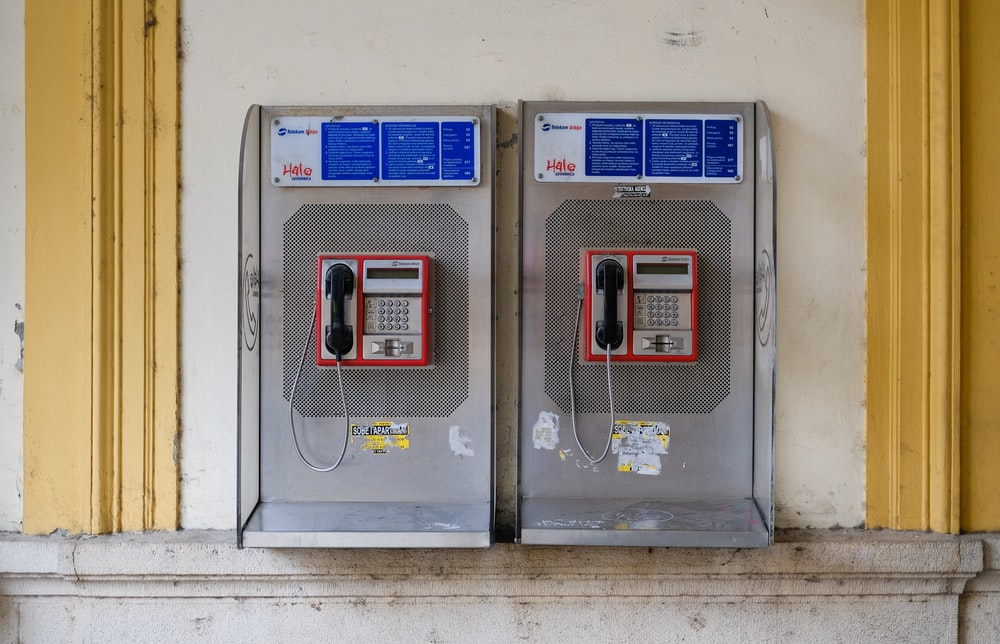 two gray-and-red coin operated telephone machine