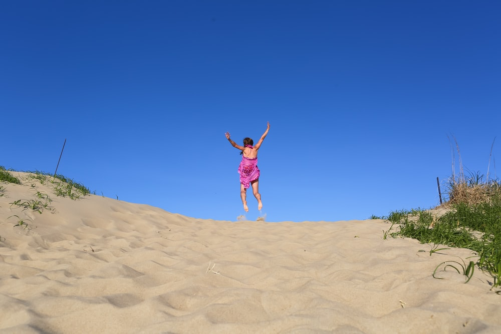 woman jumping of sand during daytime