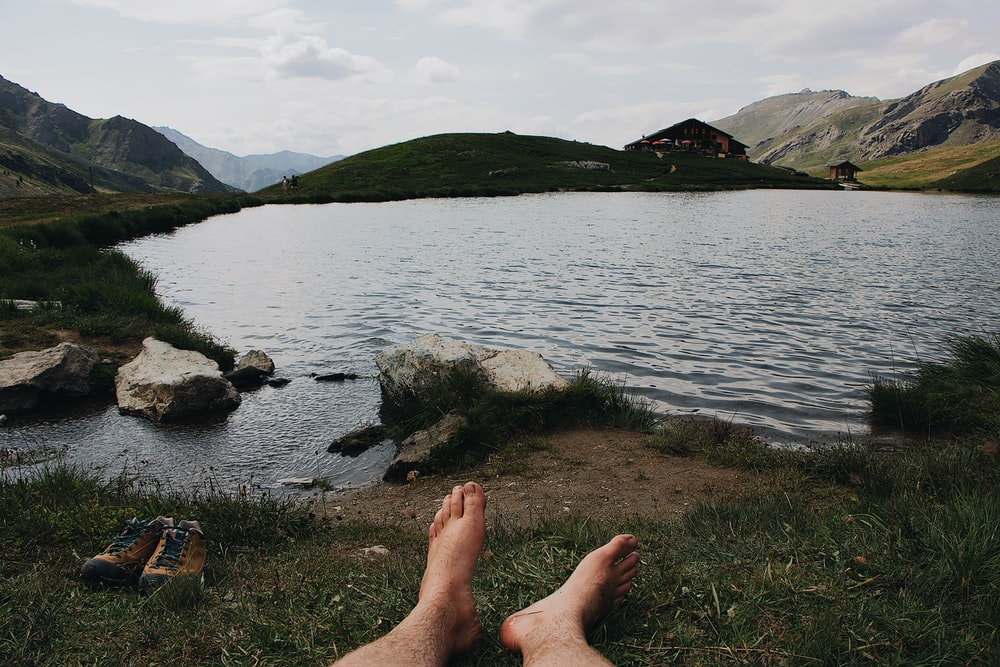 barefooted person lying on grass viewing lake and mountain