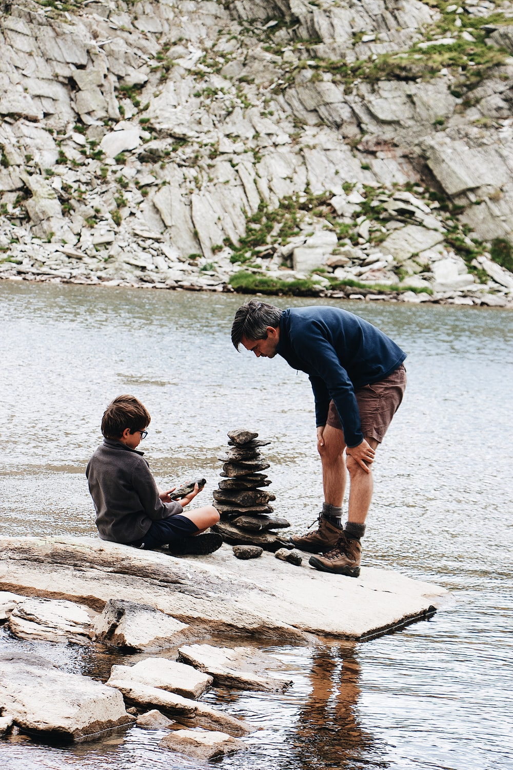 boy and man beside river during daytime
