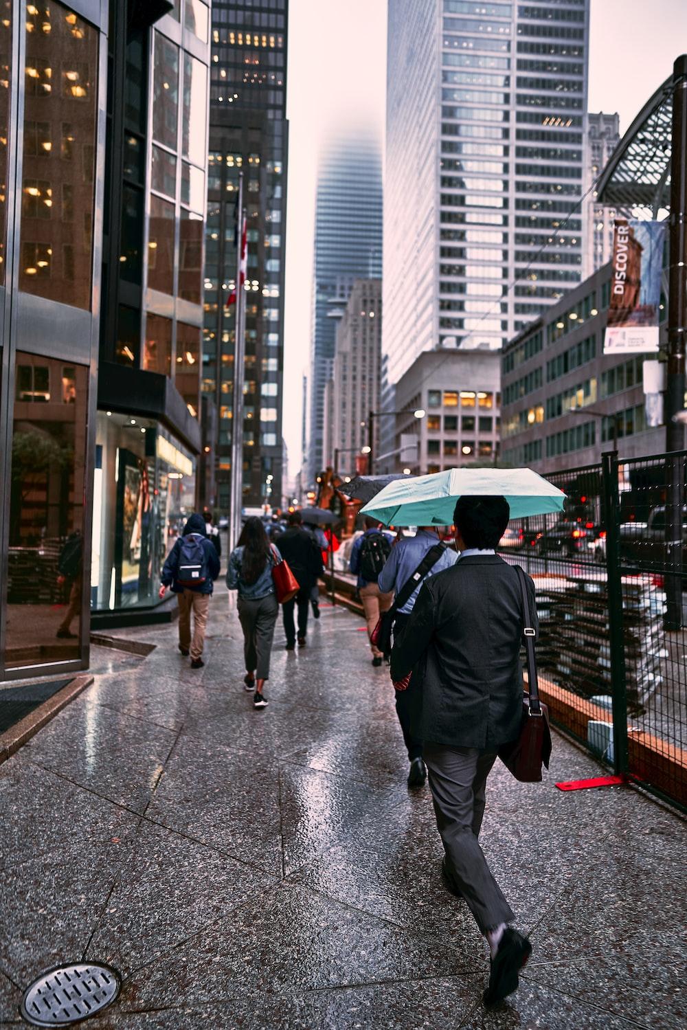 people walking beside high buildings during daytime
