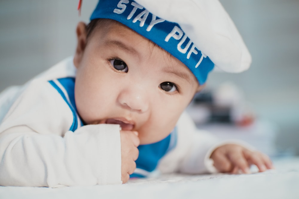 baby in white and blue navy costume