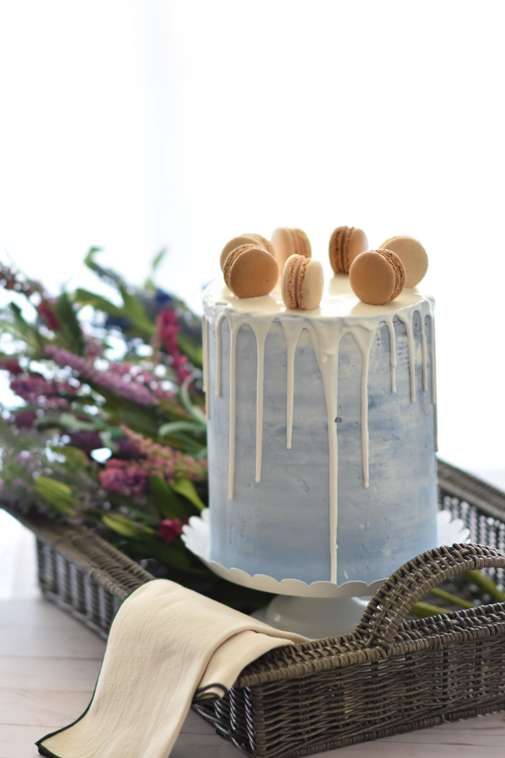 round white icing-covered cake with macaron's on top