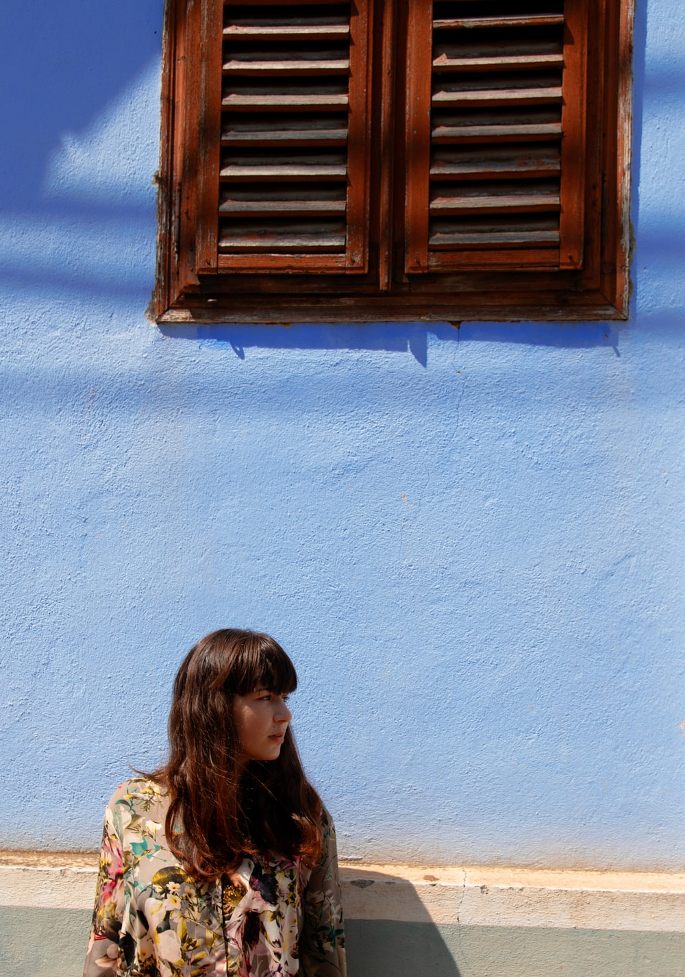 woman standing near blue painted wall and looking on her life