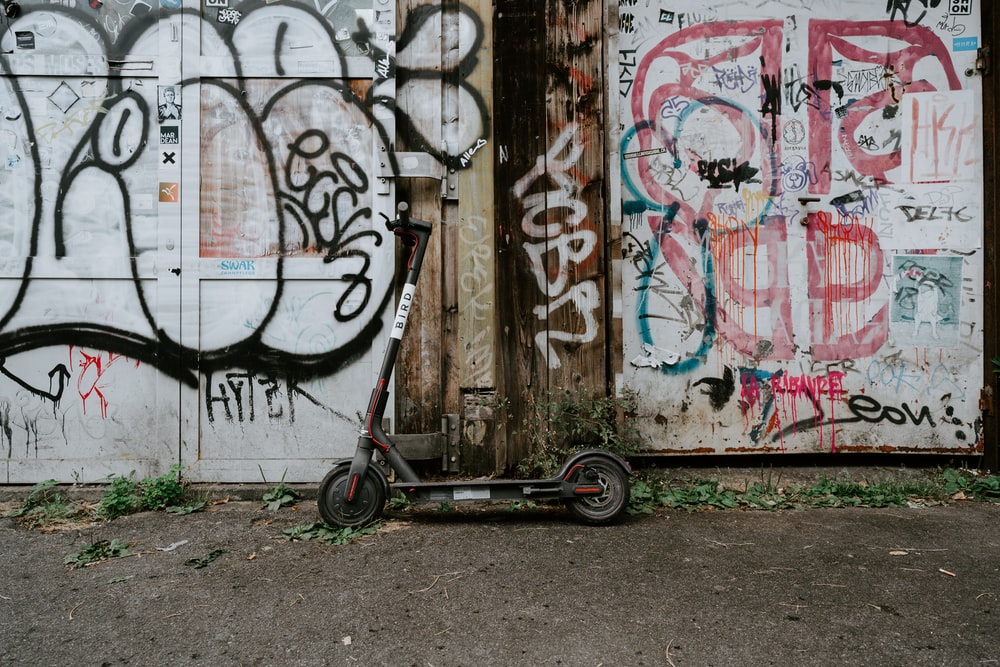 black kick scooter parked beside painted wall