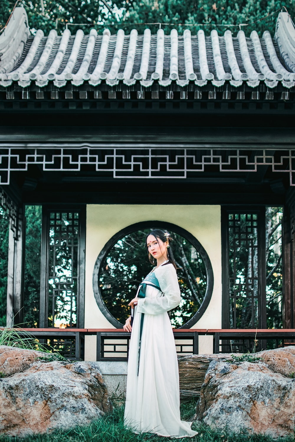 woman wearing white hakama in front of black and white temple