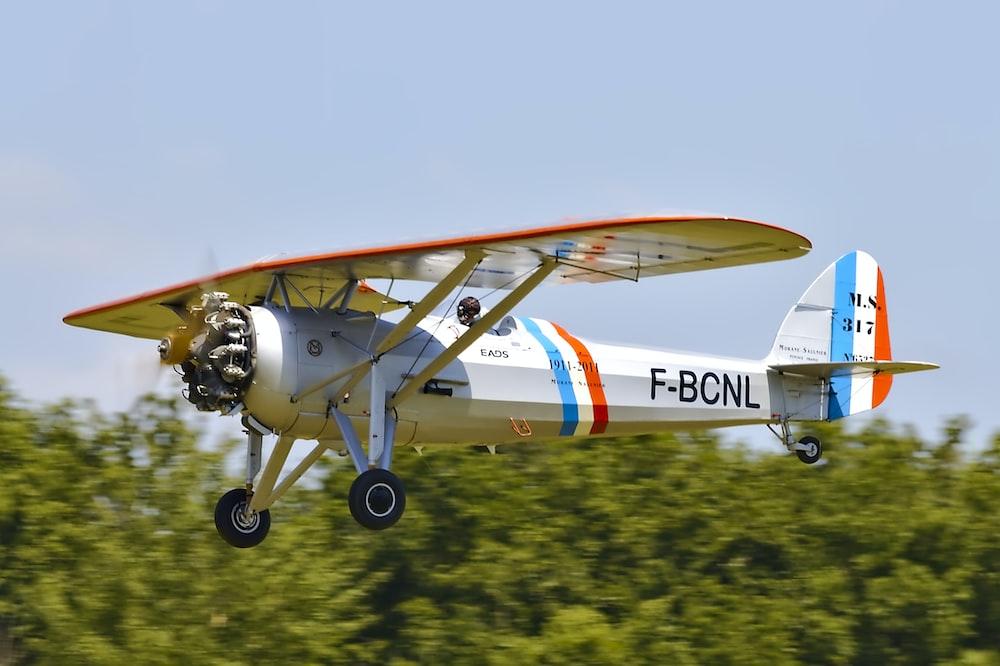 white, orange, and blue plane