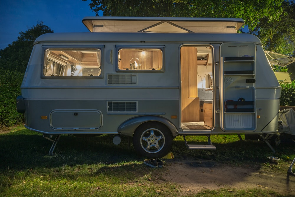 white and brown camper trailer beside tree