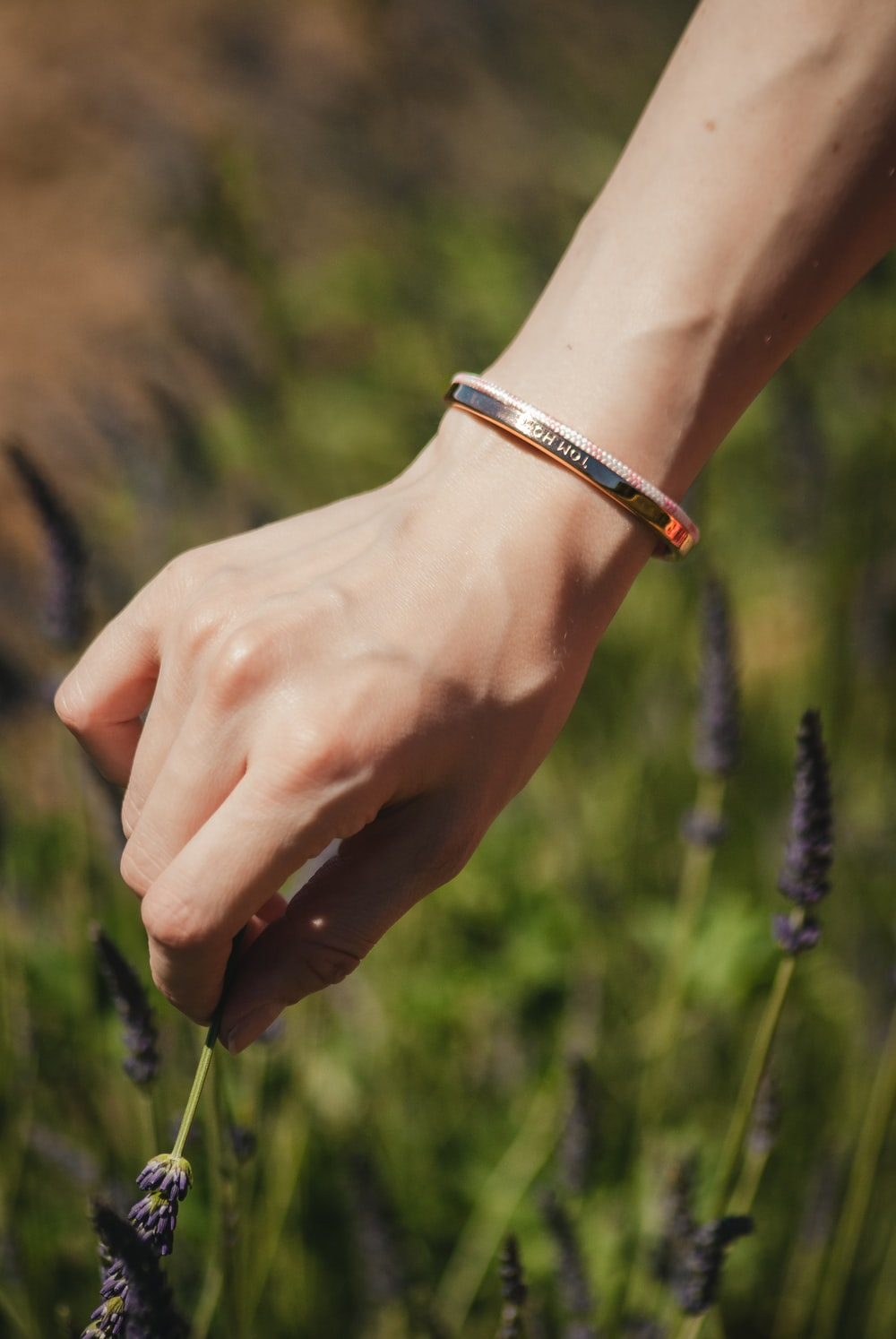 person wearing gold-colored bracelet