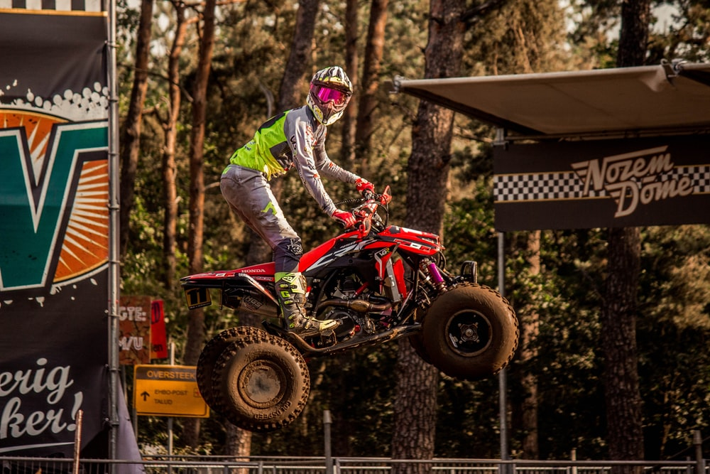 person riding red 3-wheeled ATV