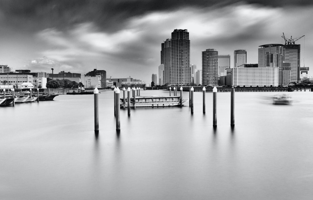 grayscale photo of body of water across city buildings