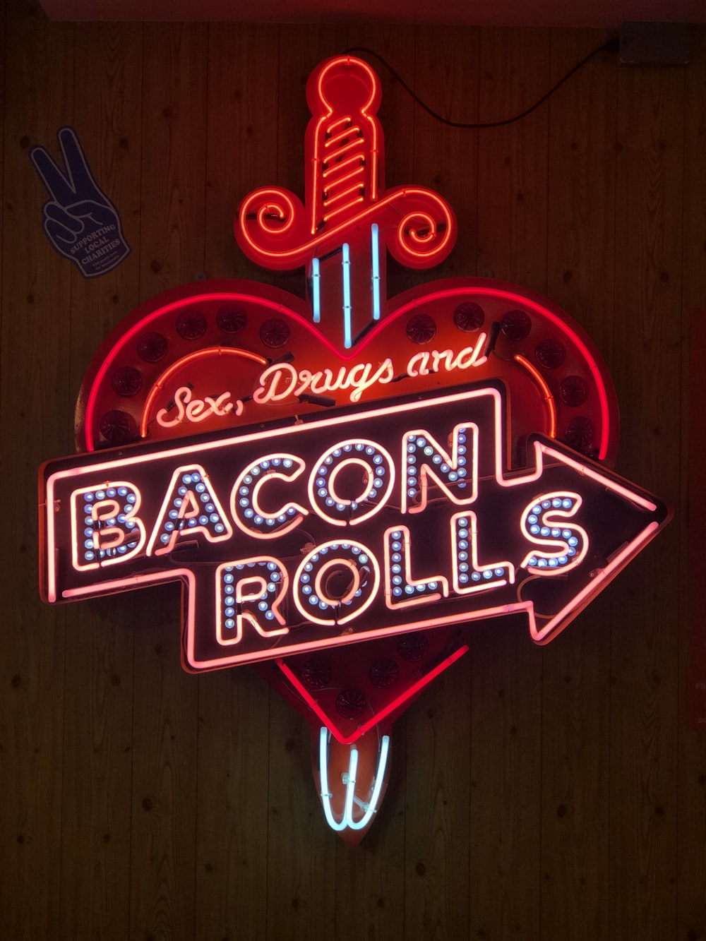 turned on Bacon Rolls neon signage on wall