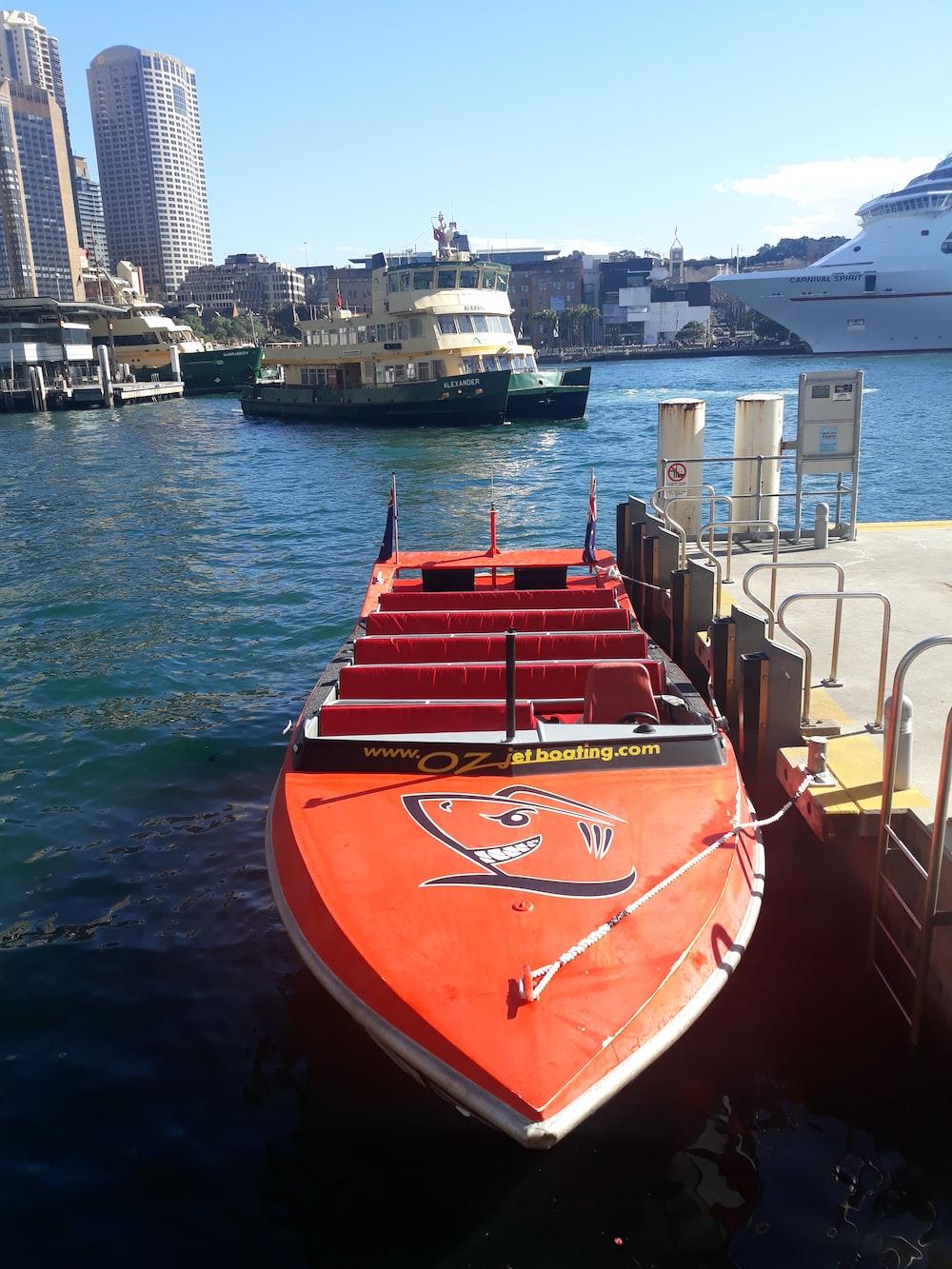 orange and white motor boat beside dock