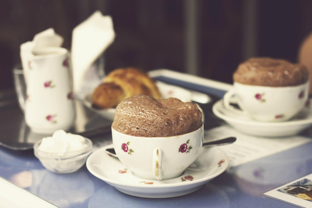 white-and-red ceramic teacups and saucers, mousse, chocolate avocado mousse