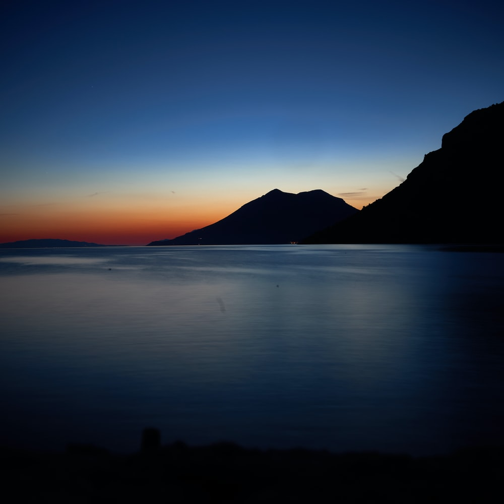 silhouette of mountain beside sea