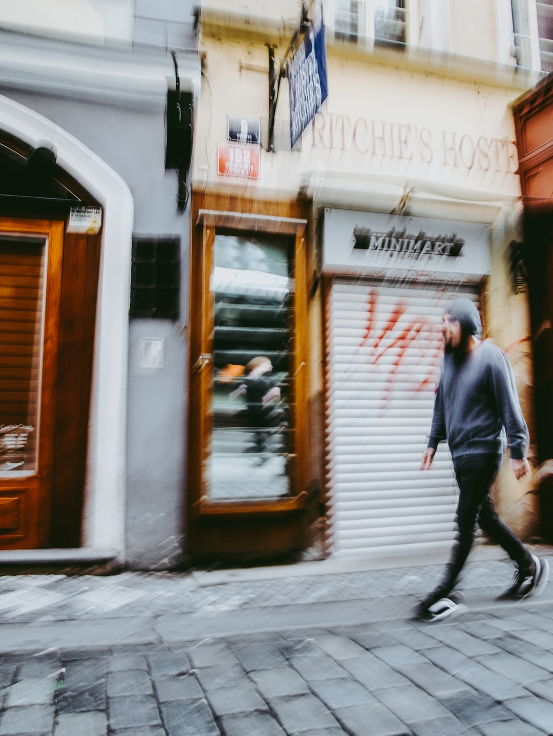 Blurred  image of  a man walking down the street.