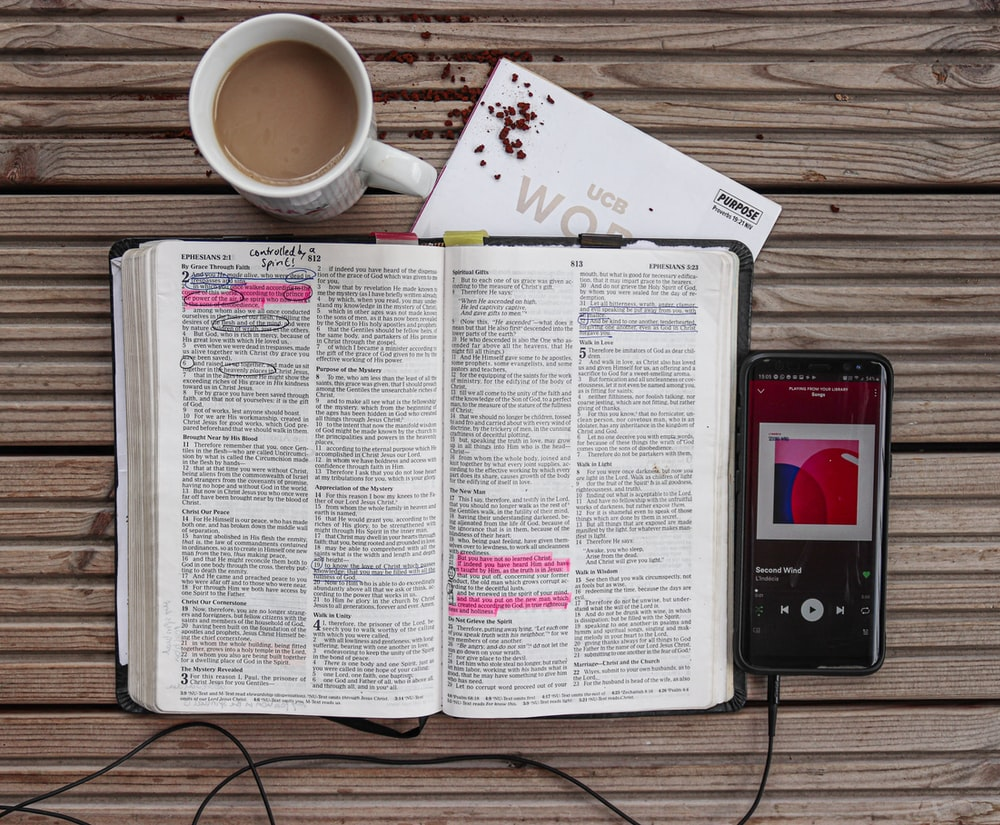 coffee in ceramic mug near open Bible and black Android smartphone
