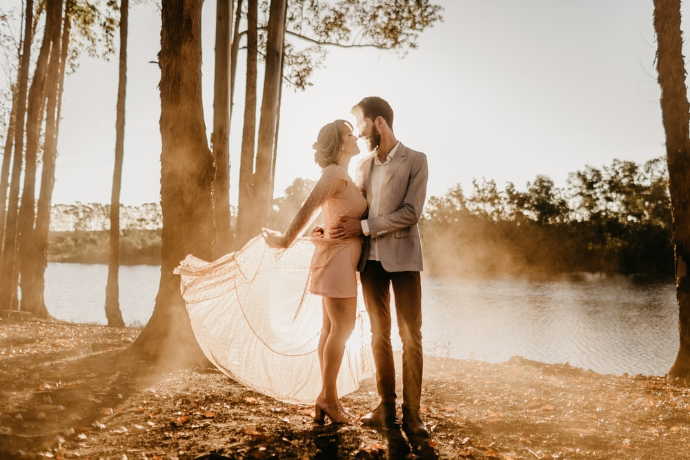 standing man and woman beside trees near body of water