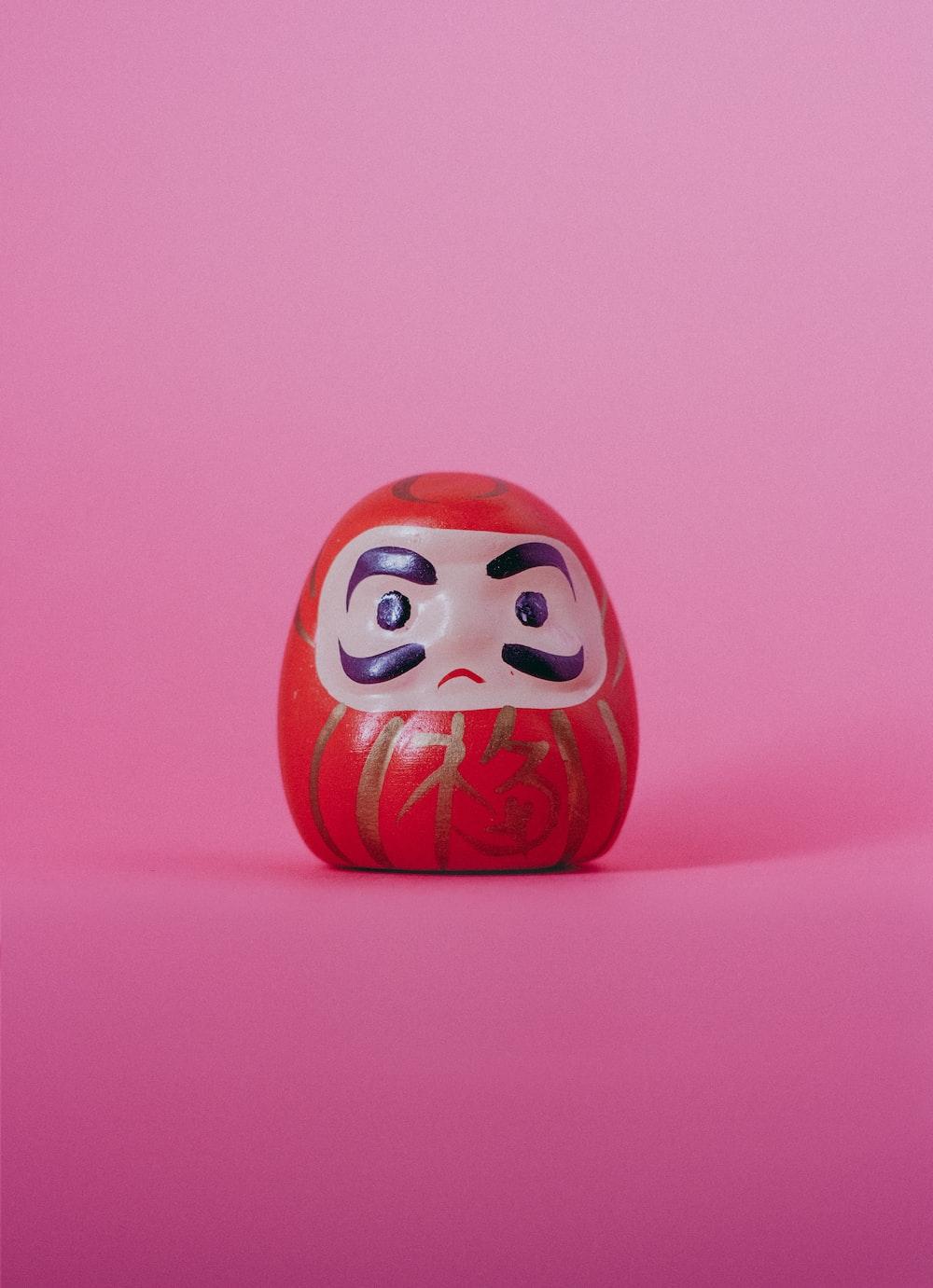 red and white Daruma doll figurine