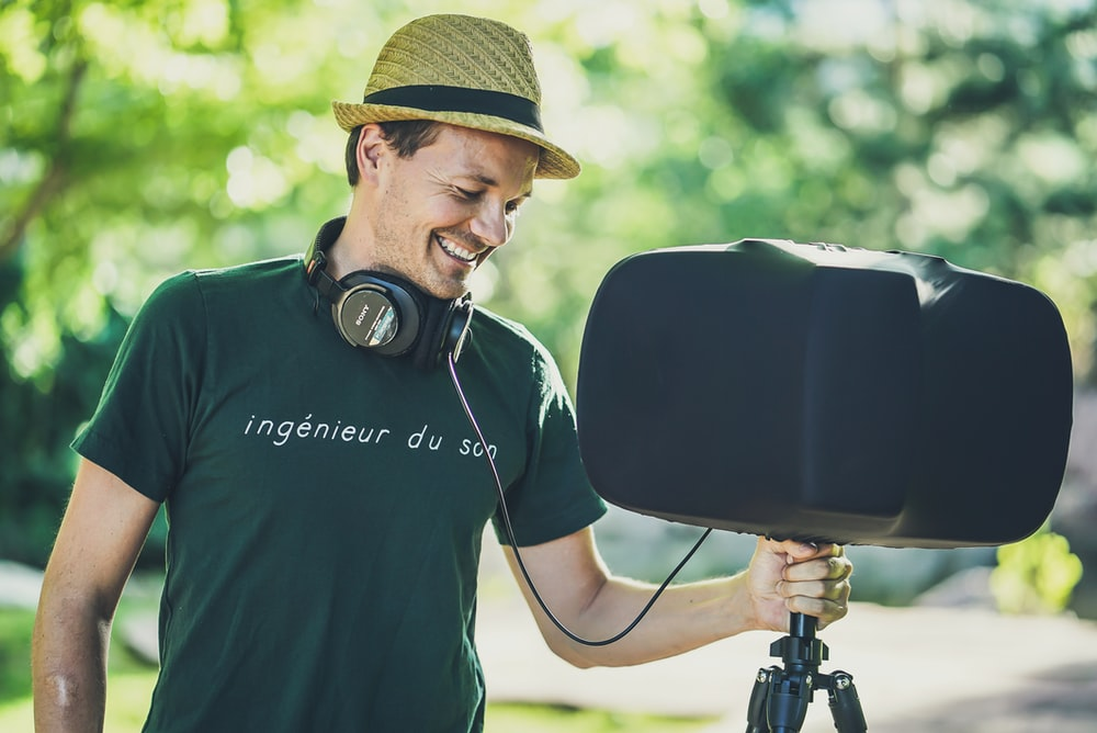 man holding black PA speakers