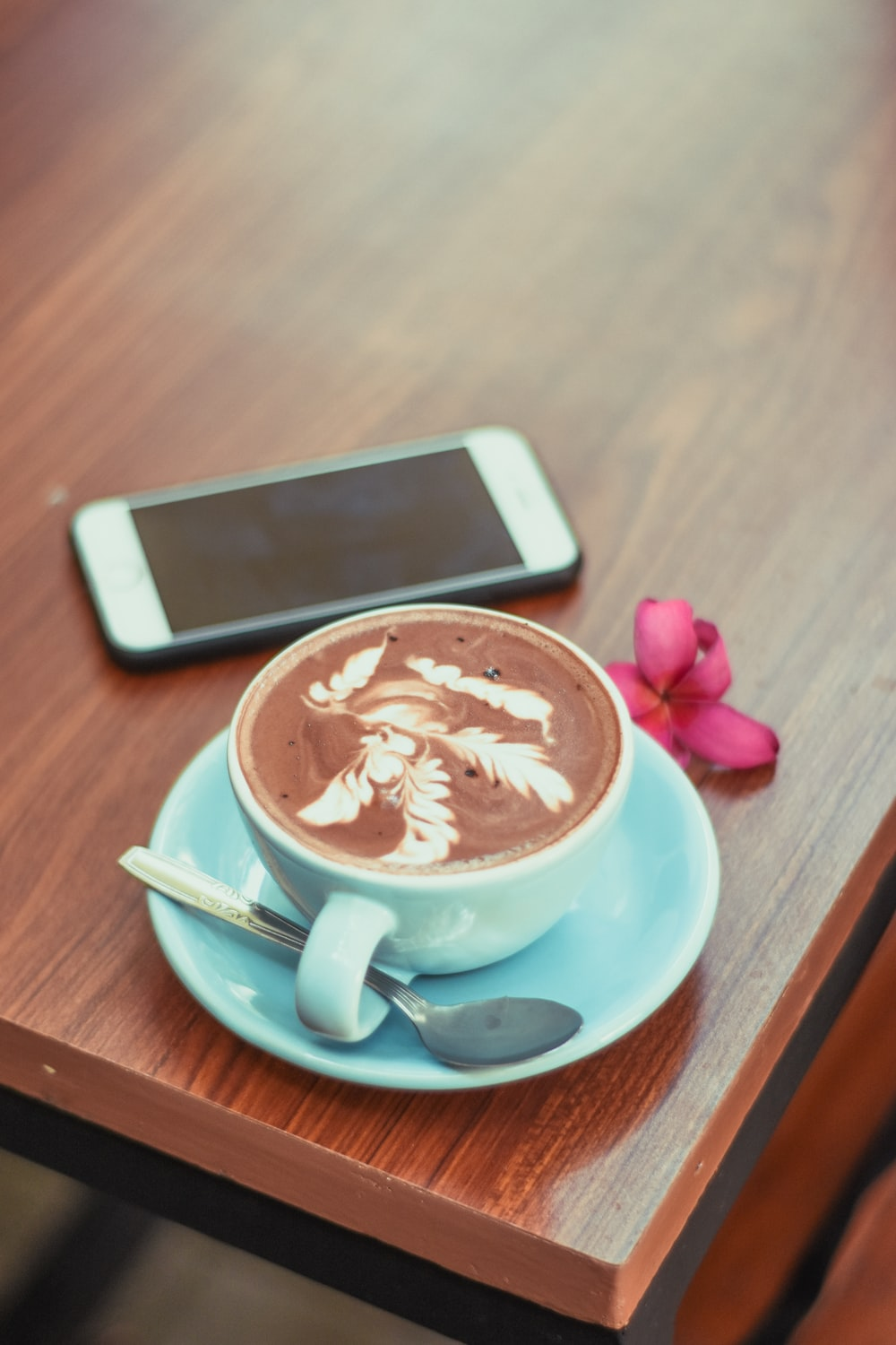 phone near a blue coffee cup with coffee and spoon close-up photography