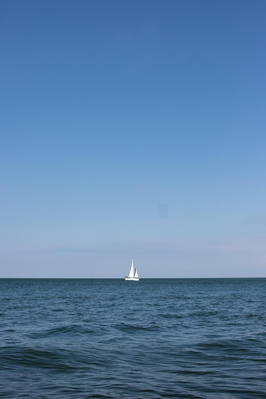 sailboat on sea under clear blue sky