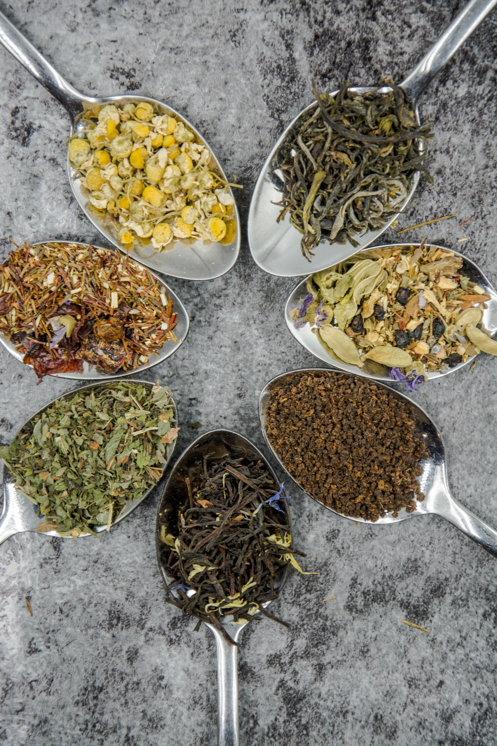 seven different spices and herbs on gray stainless steel spoons