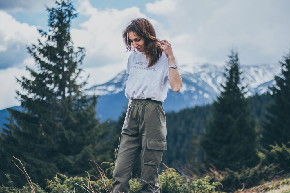 woman in grey shirt and green cargo pants standing on mountain top