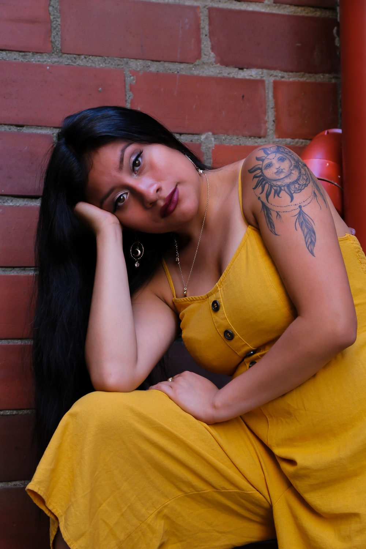 woman wearing yellow romper near red wall