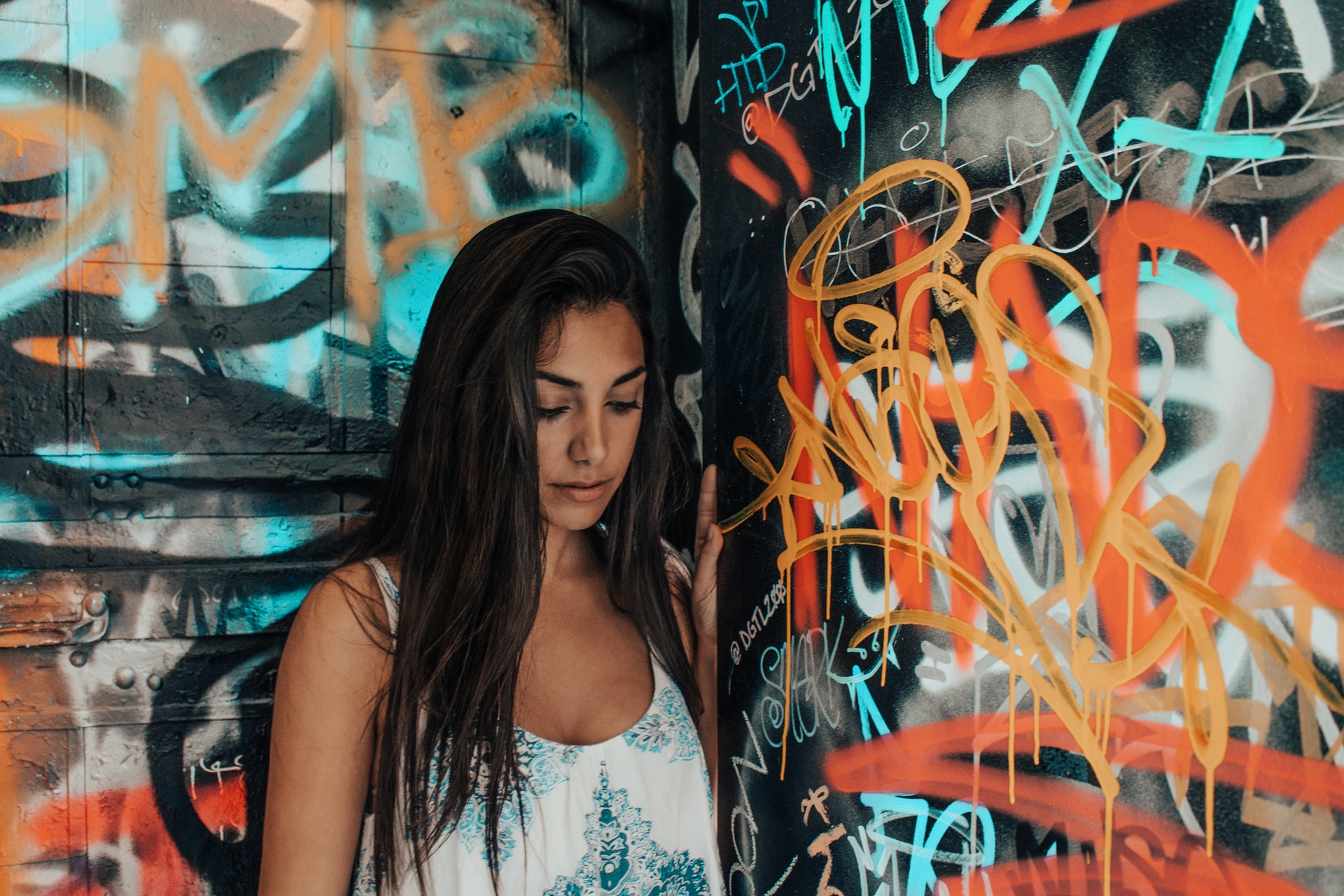 woman in white and blue tank top standing beside graffiti wall
