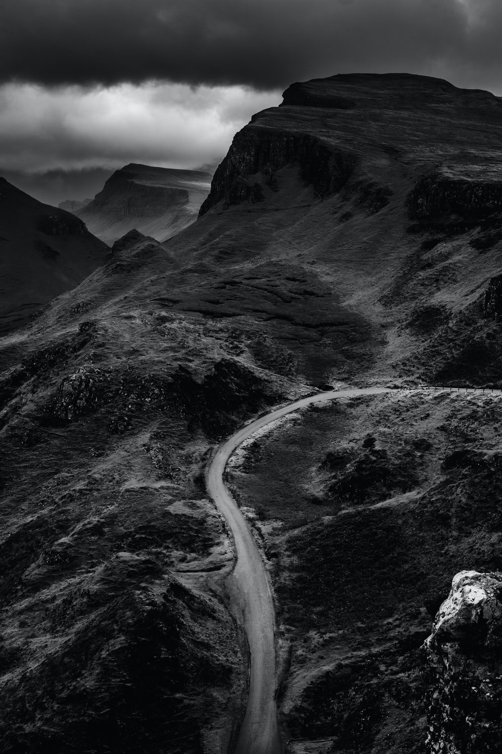 grayscale photo of road between mountain