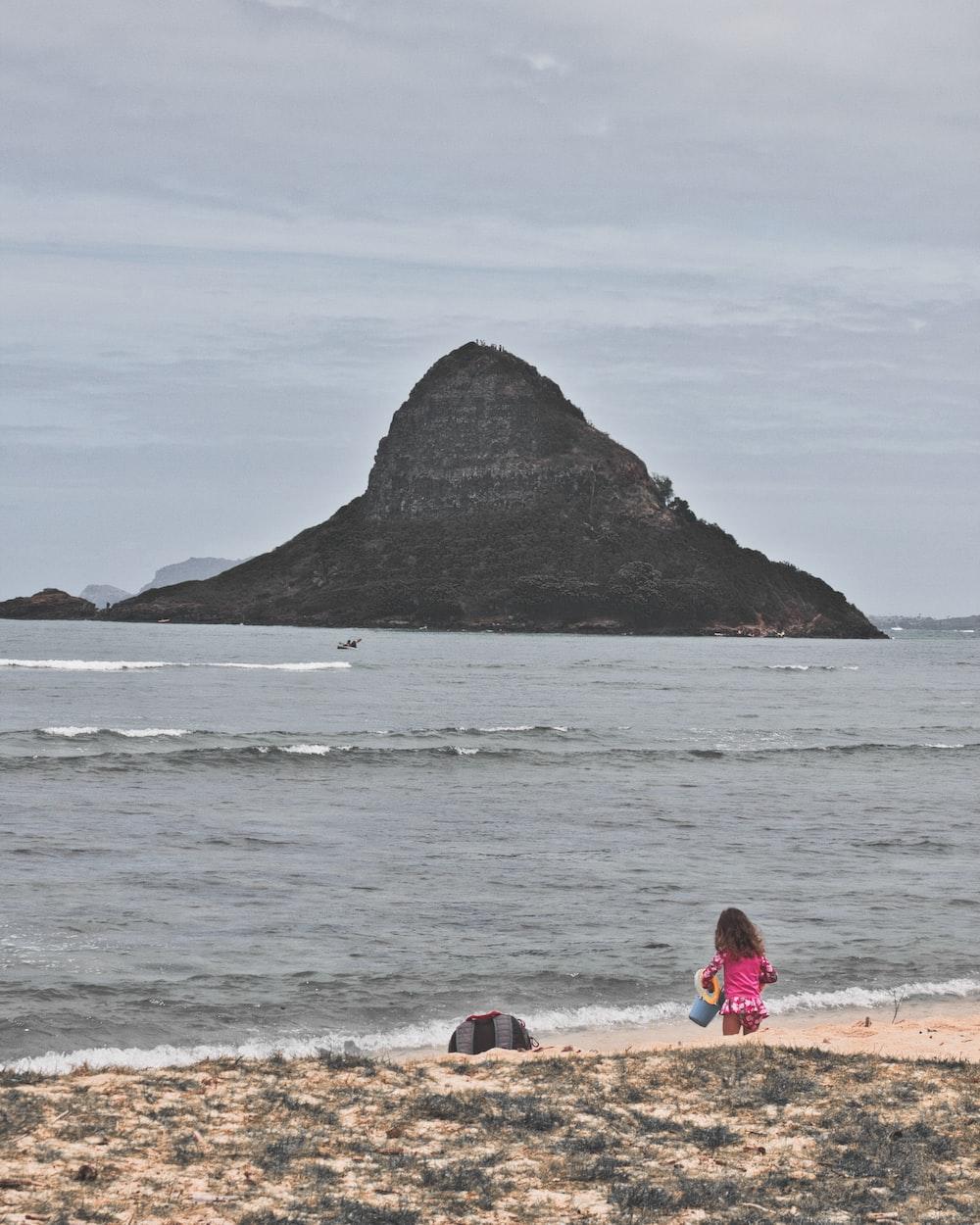 girl standing beside seashore