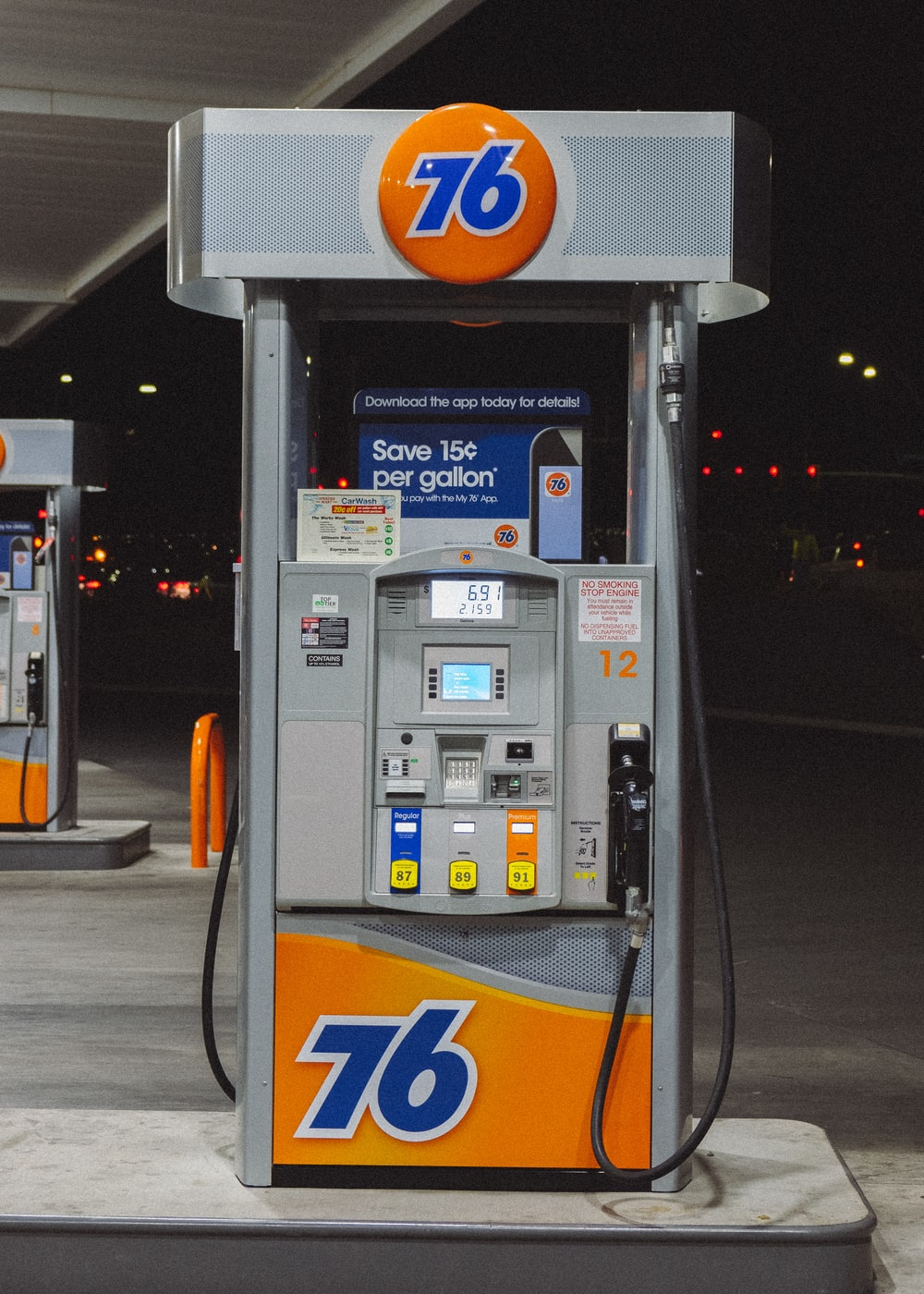 gray and orange gasoline pump