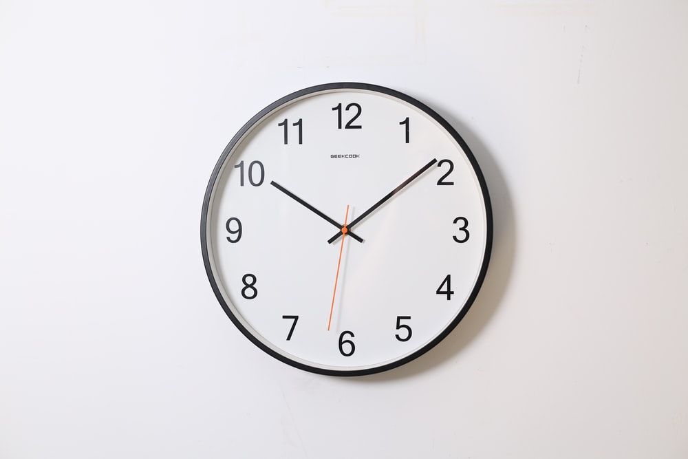 round analog wall clock pointing at 10:09
