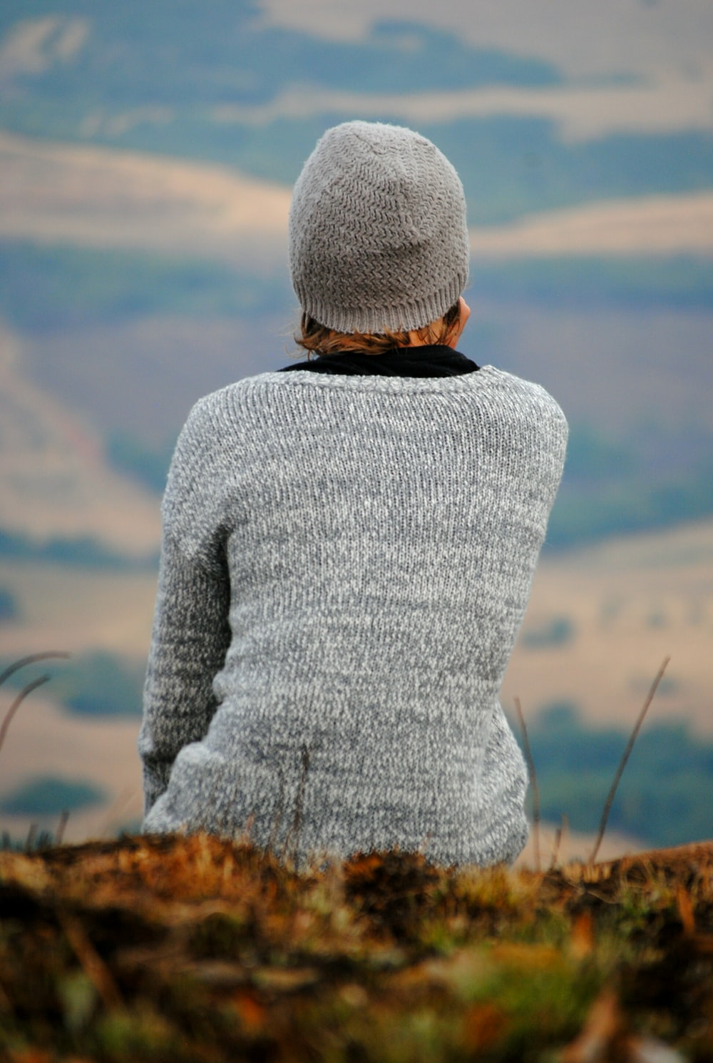 person in gray sweater sitting on green grass overlooking mountian