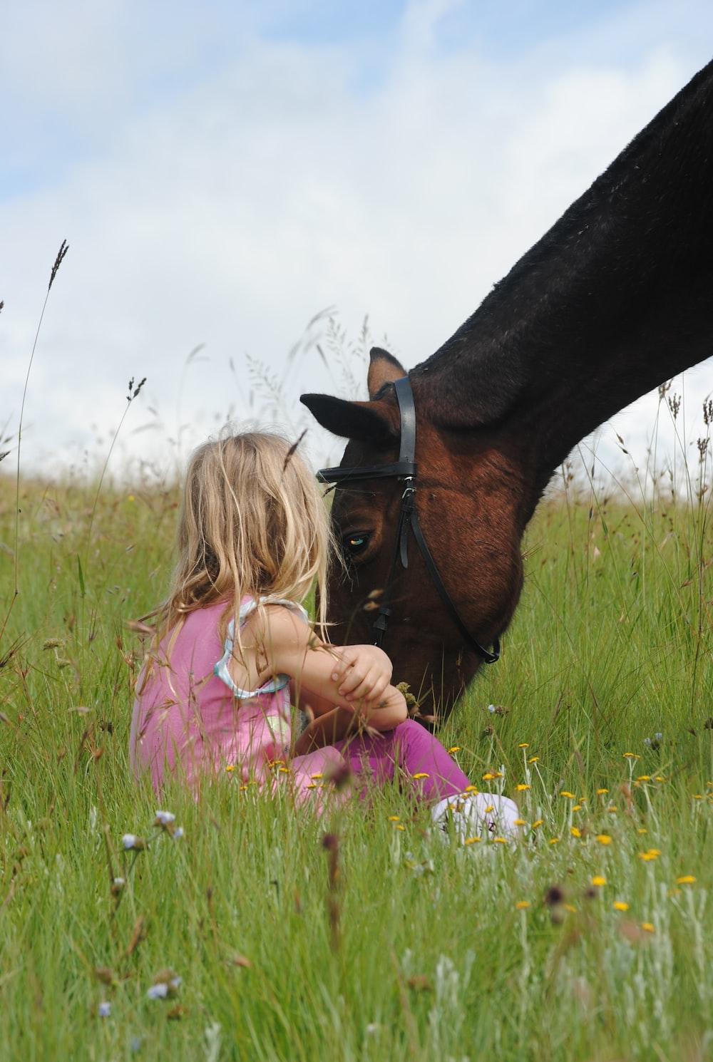kid sitting beside brown horse during daytime