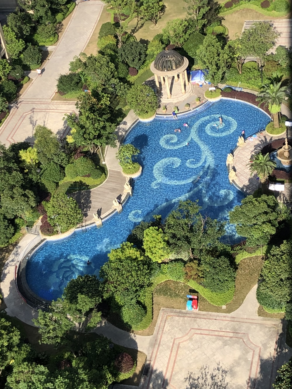 large blue and white pool surrounded by green trees at daytime