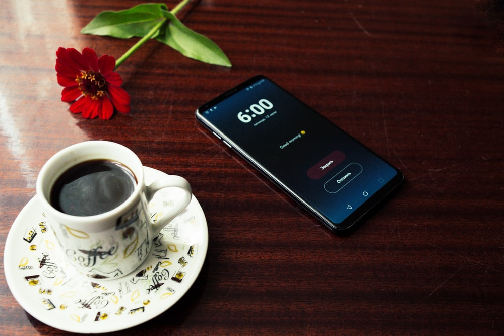 smartphone near cup of coffee on table