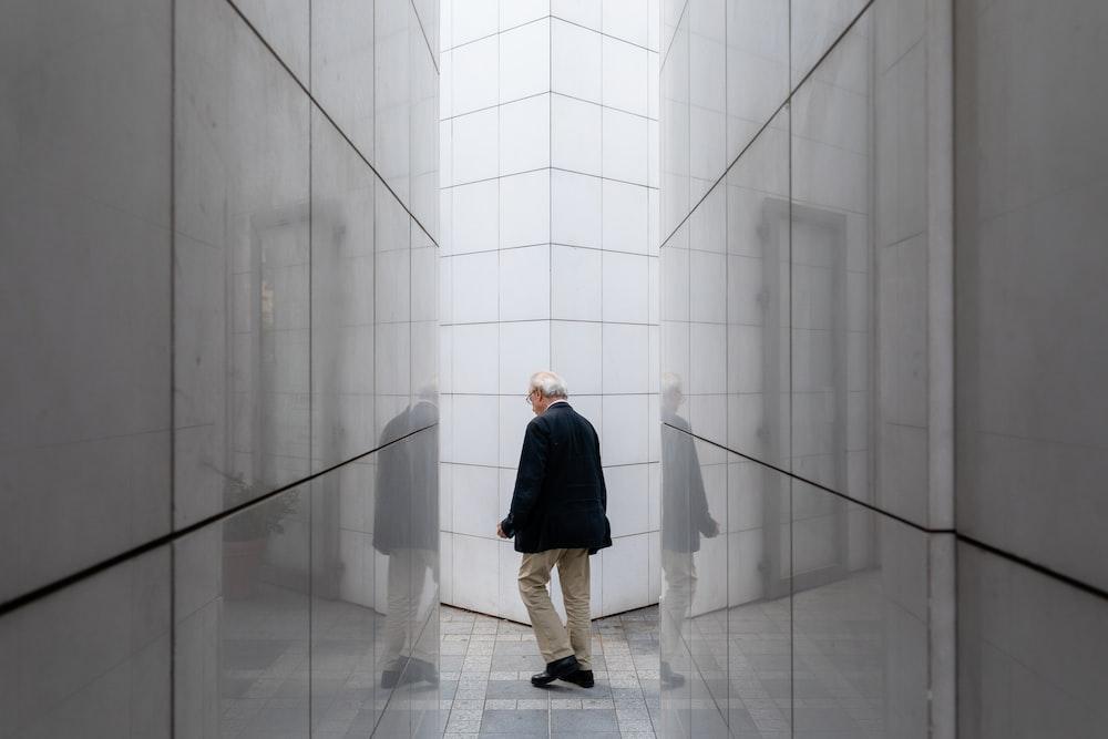 man wearing jacket standing near walls