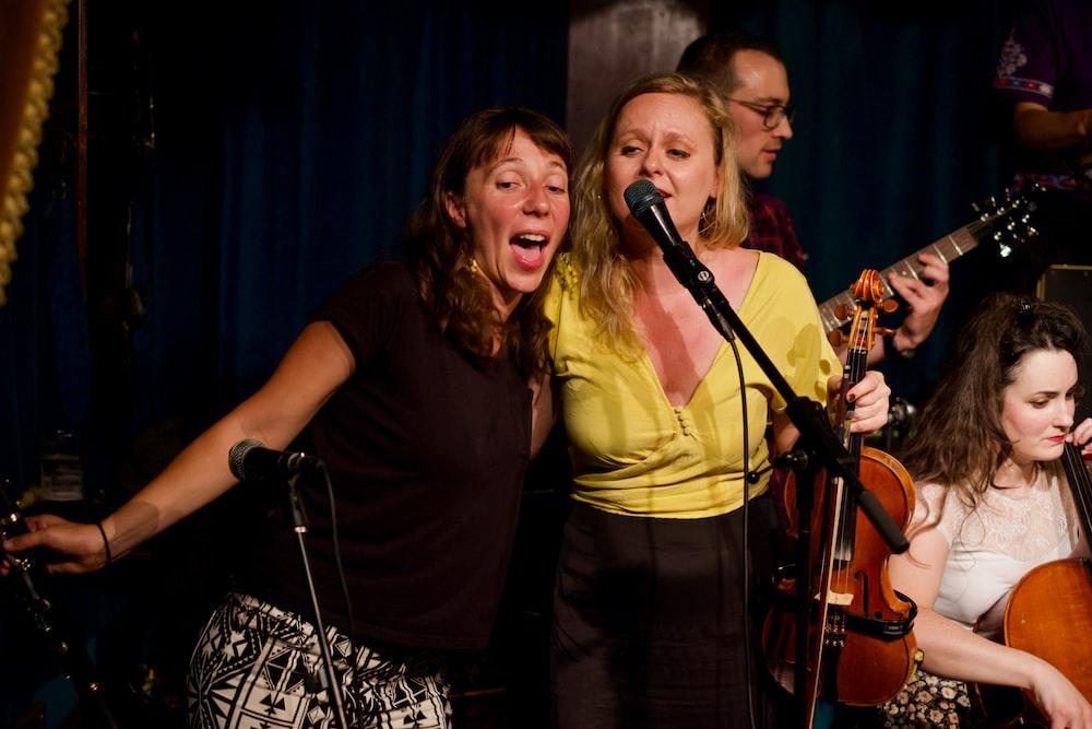 two women singing near microphone