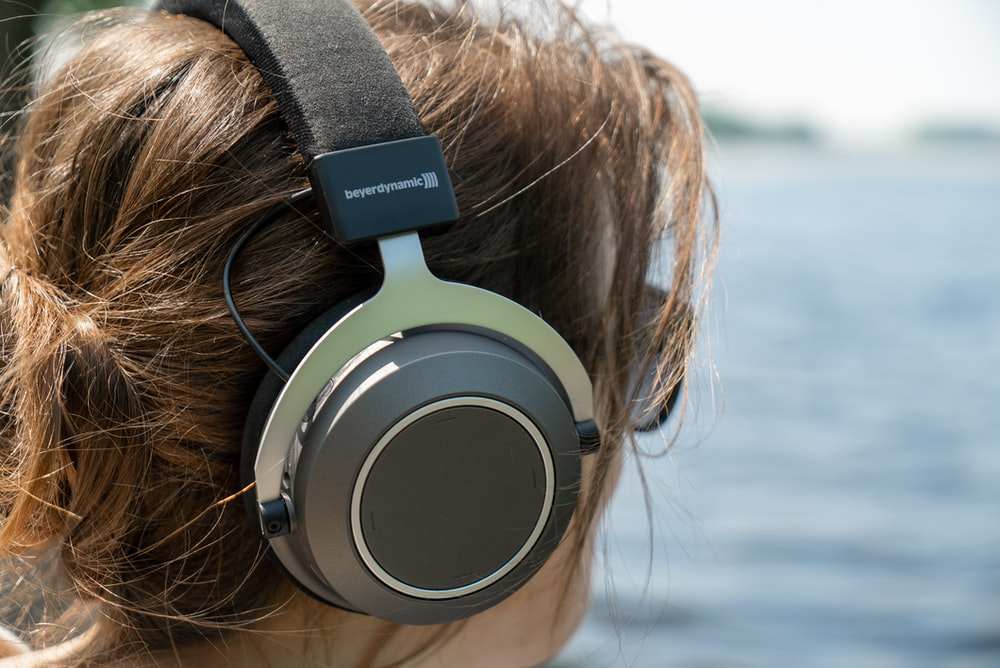 woman wearing gray and silver headphones